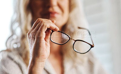 Buy stock photo Cropped shot of an unrecognizable senior businesswoman holding her spectacles at home