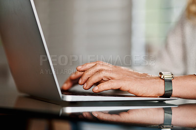 Buy stock photo Cropped shot of an unrecognizable senior businesswoman using a laptop while working from home