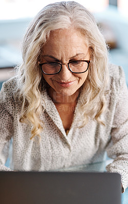 Buy stock photo Cropped shot of an attractive senior businesswoman using a laptop while working from home
