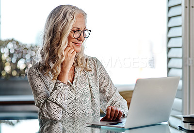 Buy stock photo Cropped shot of an attractive senior businesswoman looking thoughtful while working on a laptop at home