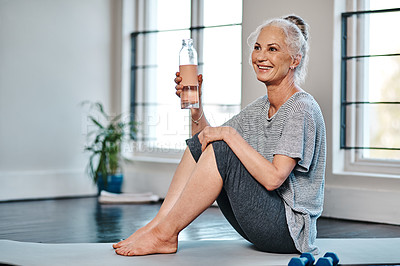 Buy stock photo Shot of a cheerful mature woman practicing yoga while having a drink of water inside of a studio during the day