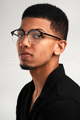 Buy stock photo Portrait of a handsome young man wearing glasses while standing against a grey background  inside of a studio