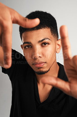 Buy stock photo Portrait of a handsome young man making a frame with his fingers while standing against a grey background inside of a studio