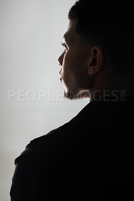 Buy stock photo Rearview shot of a handsome young man posing against a grey background inside of a studio