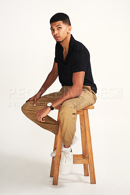 Buy stock photo Portrait of a handsome young man striking a pose while being seated on a chair against a grey background inside of a studio