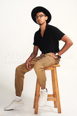 Buy stock photo Portrait of a handsome young man wearing a hat and glasses while being seated on a chair against a grey background inside of a studio
