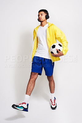 Buy stock photo Studio shot of a handsome young man listening to music while holding a soccer ball inside of a studio