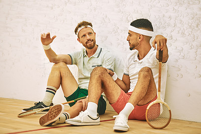 Buy stock photo Shot of two young men chatting after playing a game of squash