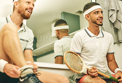 Buy stock photo Shot of two young men getting dressed in the locker room after a game of squash
