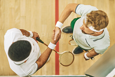 Buy stock photo High angle shot of two young men shaking hands at a squash court