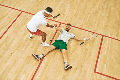 Buy stock photo High angle shot of a young man helping his friend up while playing a fame of squash