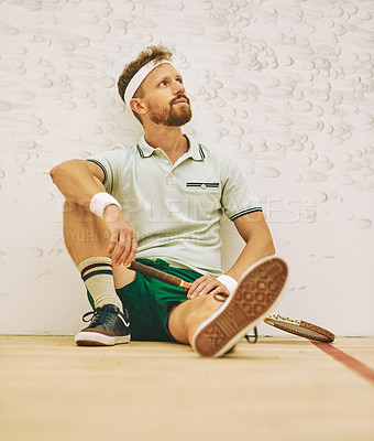 Buy stock photo Shot of a young man taking a break after playing a game of squash