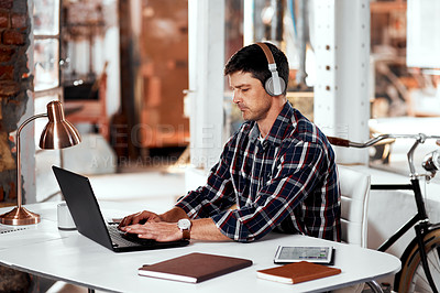 Buy stock photo Cropped shot of a handsome young businessman listening to music while working on a laptop in an office inside his workshop