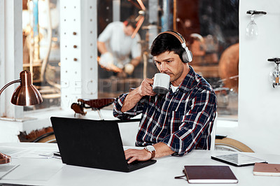 Buy stock photo Cropped shot of a handsome young businessman drinking coffee while working on a laptop in an office inside his workshop