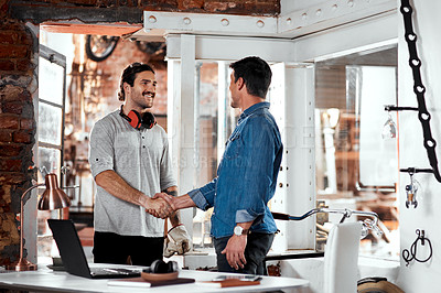 Buy stock photo Cropped shot of two young businessmen shaking hands in an office inside their workshop