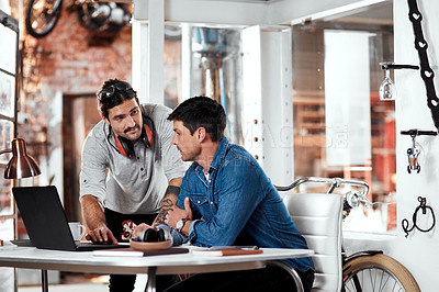 Buy stock photo Cropped shot of two young businessmen working together in an office inside their workshop