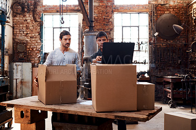 Buy stock photo Cropped shot of two young businessmen using a laptop while sorting out orders and deliveries inside their workshop