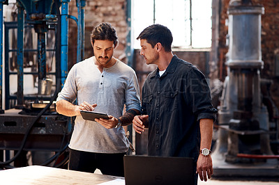 Buy stock photo Cropped shot of two handsome young using a digital tablet while working together inside their workshop
