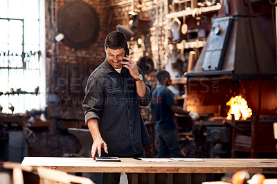 Buy stock photo Cropped shot of a handsome young businessman making a   while working inside his workshop