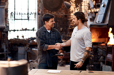 Buy stock photo Cropped shot of two handsome young businessmen shaking hands while working together inside a workshop