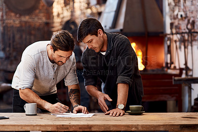 Buy stock photo Cropped shot of two handsome young businessmen working together inside their workshop