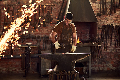 Buy stock photo Cropped shot of a handsome young metal worker hitting a hot metal rod with a sledgehammer in a welding workshop