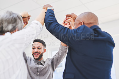 Buy stock photo Shot of a group of businesspeople holding hands together in a huddle