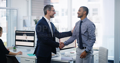 Buy stock photo Shot of two businessmen shaking hands in an office with their colleagues in the background