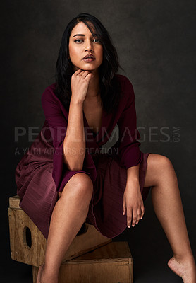 Buy stock photo Cropped portrait of an attractive young woman sitting alone and posing flirtatiously against a dark background in the studio