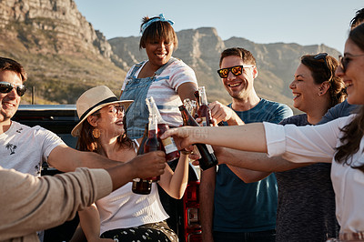 Buy stock photo Cropped shot of a group of young friends making a toast with beer bottles at the beach