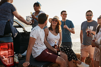 Buy stock photo Cropped shot of a group of young friends drinking beer while hanging out together at the beach