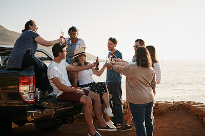 Buy stock photo Cropped shot of a group of young friends making a toast with beer bottles while hanging out together at the beach