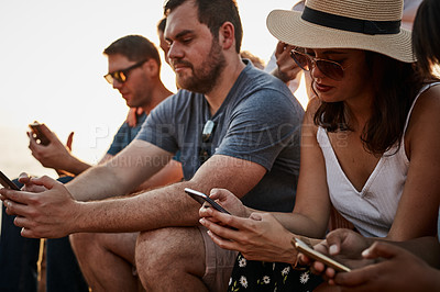 Buy stock photo Cropped shot of a group of young friends using their smartphones while sitting together at the beach