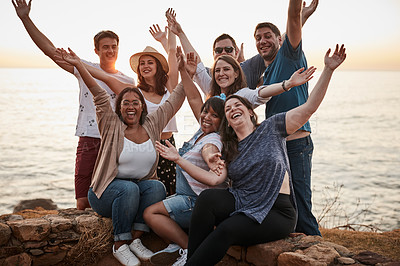 Buy stock photo Cropped portrait of a group of young friends cheering with their arms raised while hanging out at the beach during the day