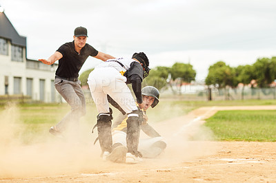 Buy stock photo Full length shot of a young baseball player sliding on the pitch and safely reaching base during a game outdoors