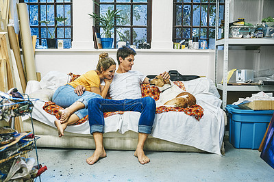 Buy stock photo Shot of a happy young couple relaxing together with their dog on the sofa at home