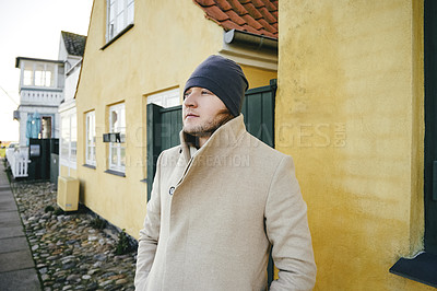 Buy stock photo Cropped shot of a handsome young man wearing winter attire standing outside his house