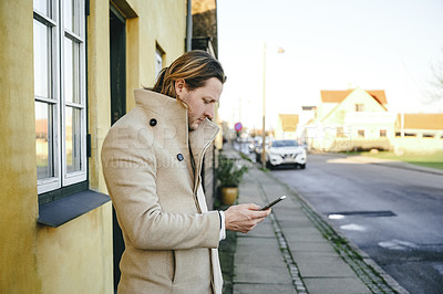 Buy stock photo Cropped shot of a handsome young man using his cellphone while standing outside his house