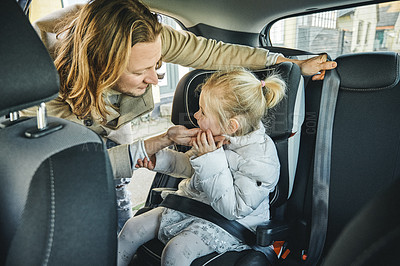 Buy stock photo Shot of a young father safely putting his daughter in her car seat before traveling together in a car