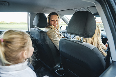 Buy stock photo Shot of a happy young family going on a road trip together in their car