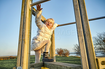 Buy stock photo Shot of an adorable little girl playing on a jungle gym outdoors at a park