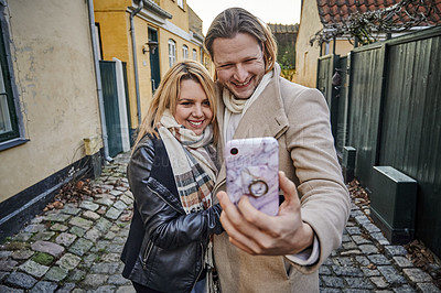 Buy stock photo Portrait of a happy young couple taking selfies outdoors while traveling together in a foreign town