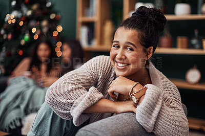 Buy stock photo Shot of a beautiful young woman relaxing on the sofa with her friends in the background during Christmas at home