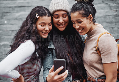 Buy stock photo Cropped portrait of an attractive group of sisters standing together and taking a selfie with a cellphone in the city