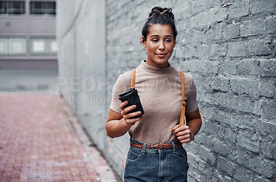 Buy stock photo Cropped shot of an attractive teenage girl holding a cup of coffee and walking through the city alone