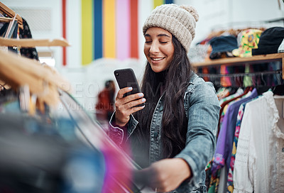 Buy stock photo Cropped shot of an attractive teenage girl standing alone and using her cellphone while in a clothing store alone