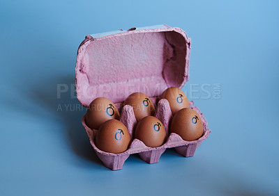 Buy stock photo Studio shot of a box against a blue background containing half a dozen eggs with the male symbol drawn on it