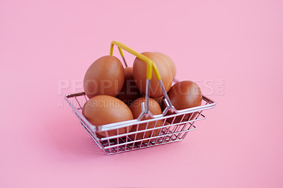 Buy stock photo Studio shot of chicken eggs in a basket against a pink background
