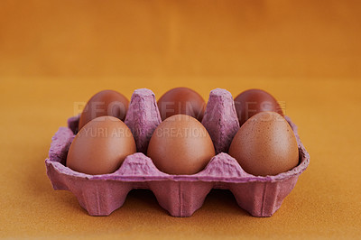 Buy stock photo Studio shot of six chicken eggs in a carton against a colored background