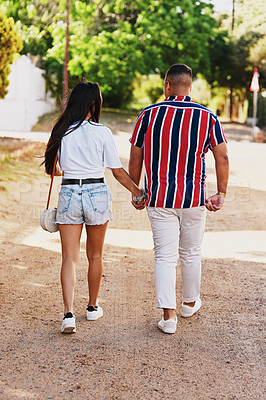 Buy stock photo Rearview shot of a young couple holding hands while walking outdoors